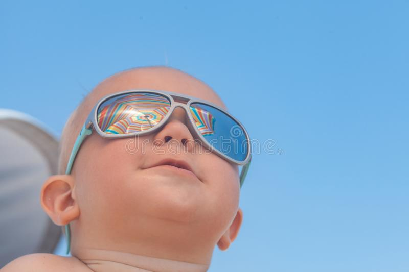 Happy funny smiling cute baby boy with sunglasses. Adorable Happy funny smiling cute baby boy with sunglasses on the beach stock images
