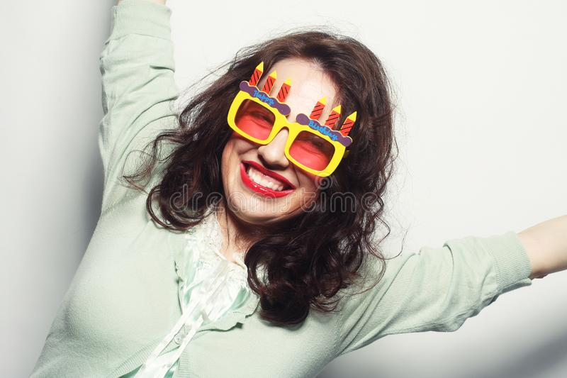 Happy funny woman. Positive energy portrait of happy funny woman with bright holiday glasses stock photography