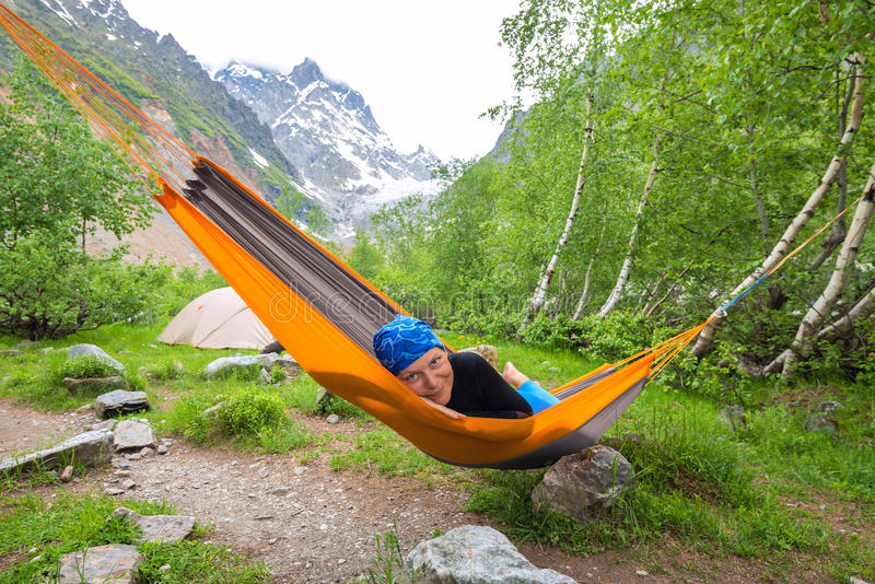 Happy funny woman traveler relaxing in hammock in the mountains stock image