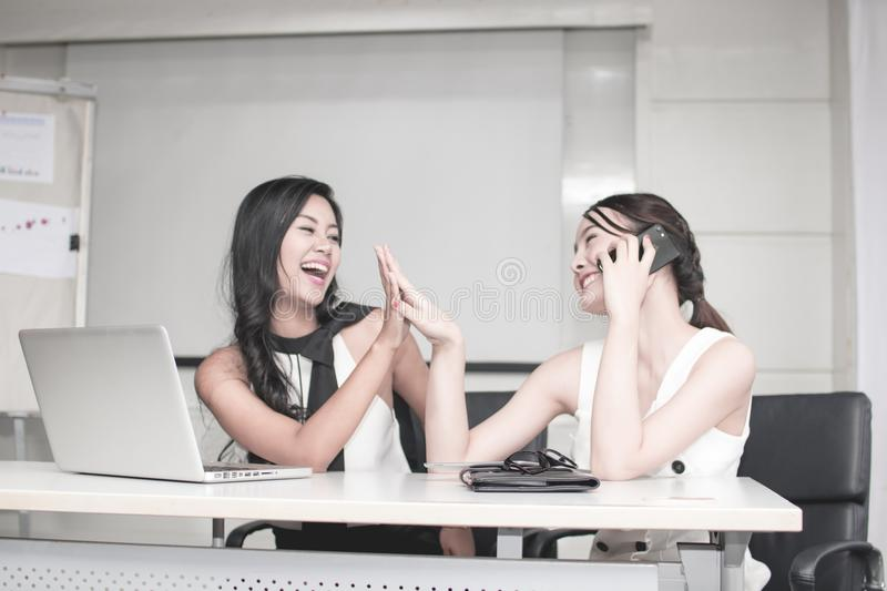 Happy and funny women take team by clapping hand together in off. Ice and enjoy talking to gossip in office royalty free stock photography
