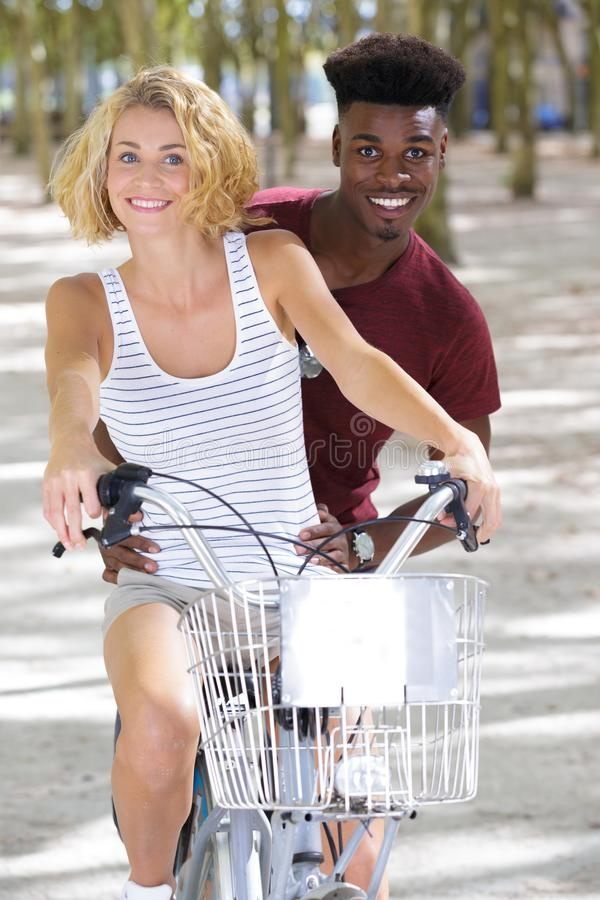 Happy funny young couple riding on bicycle stock photography