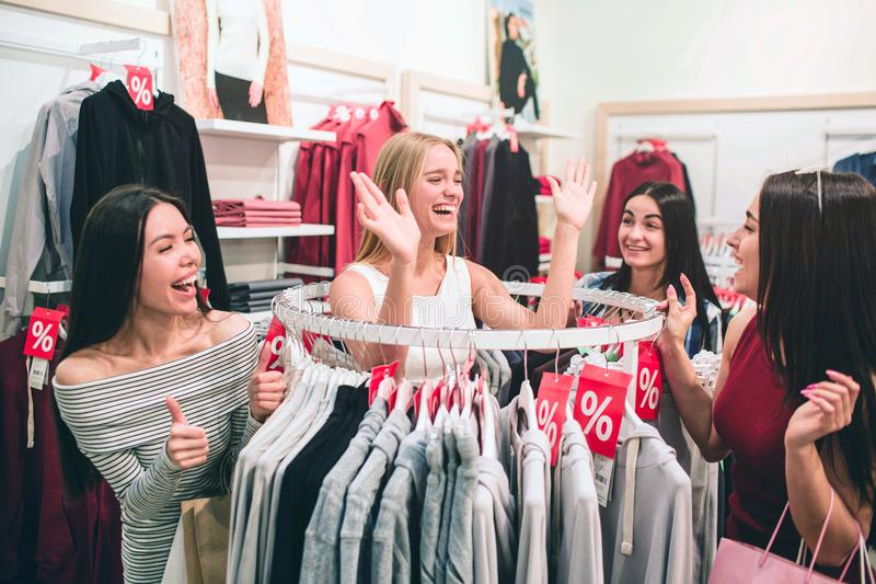 Happy and funny young women are standing together near round hanger and having some fun. They are waving with their royalty free stock image