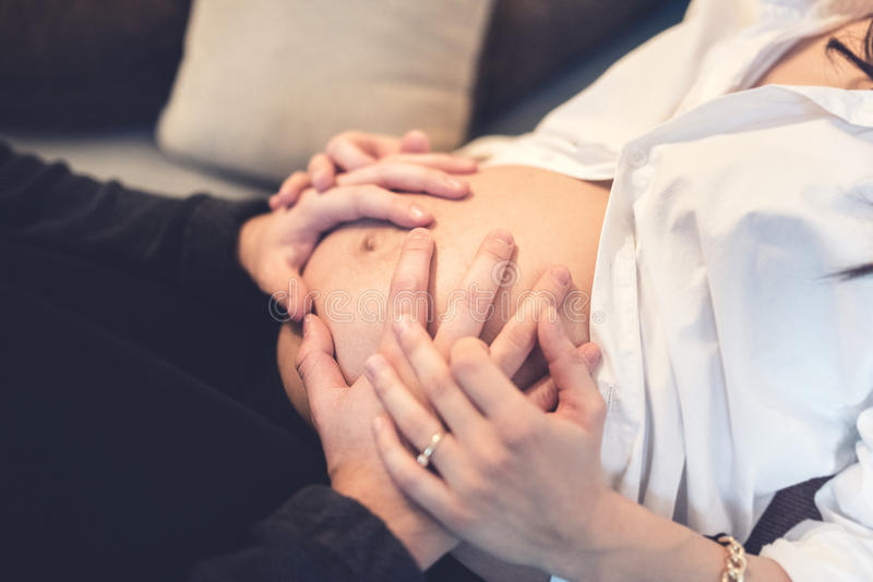 Happy future father holding hands and touching belly of wife. Happy future father holding hands and touching belly of pregnant wife, maternity concept royalty free stock images
