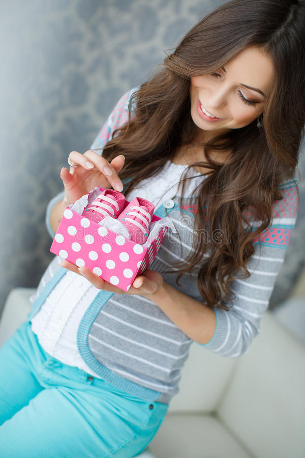 Happy future mother with pink booties in hand royalty free stock photos