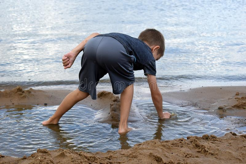 Boy plays dirt on the river bank in  summer. Active children`s holiday outdoor stock images