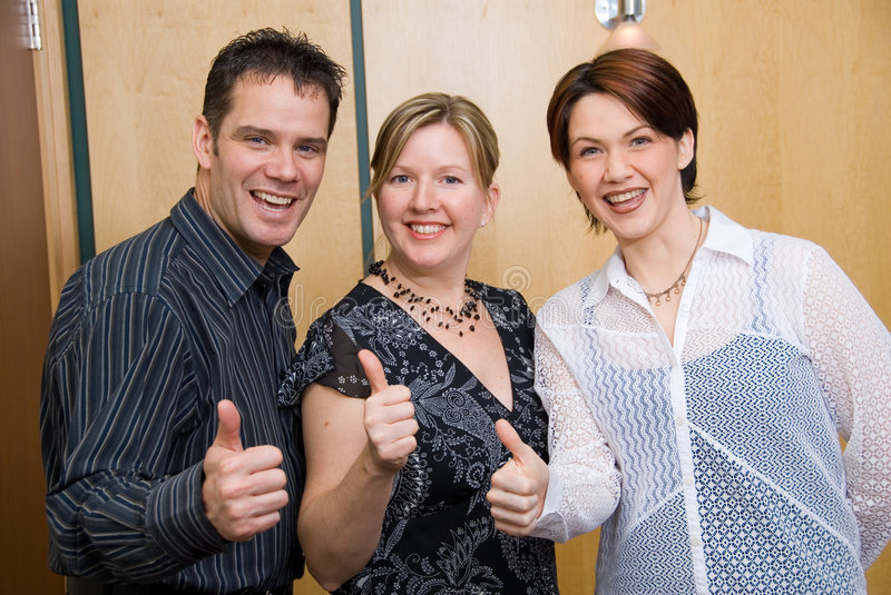 Happy gang. 3 colleagues with their thumbs up stock photography