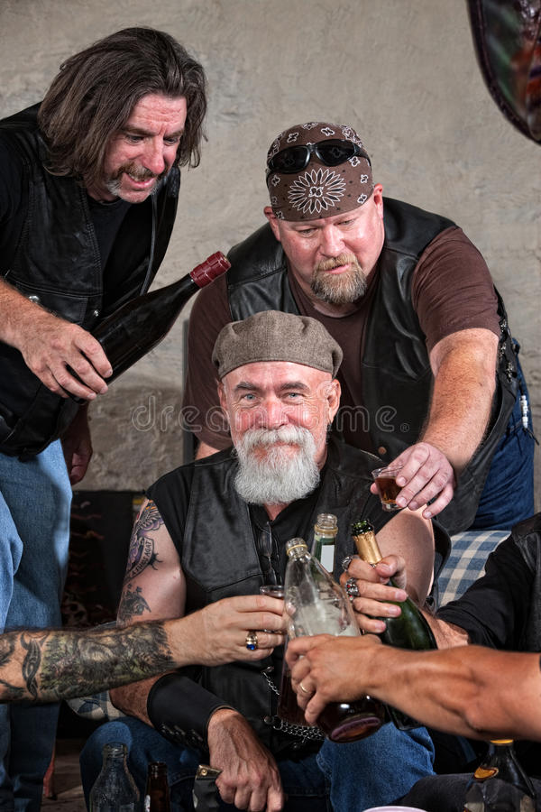 Happy Gang Members with Alcohol. Smiling gang members toasting with bottle of liquor stock image