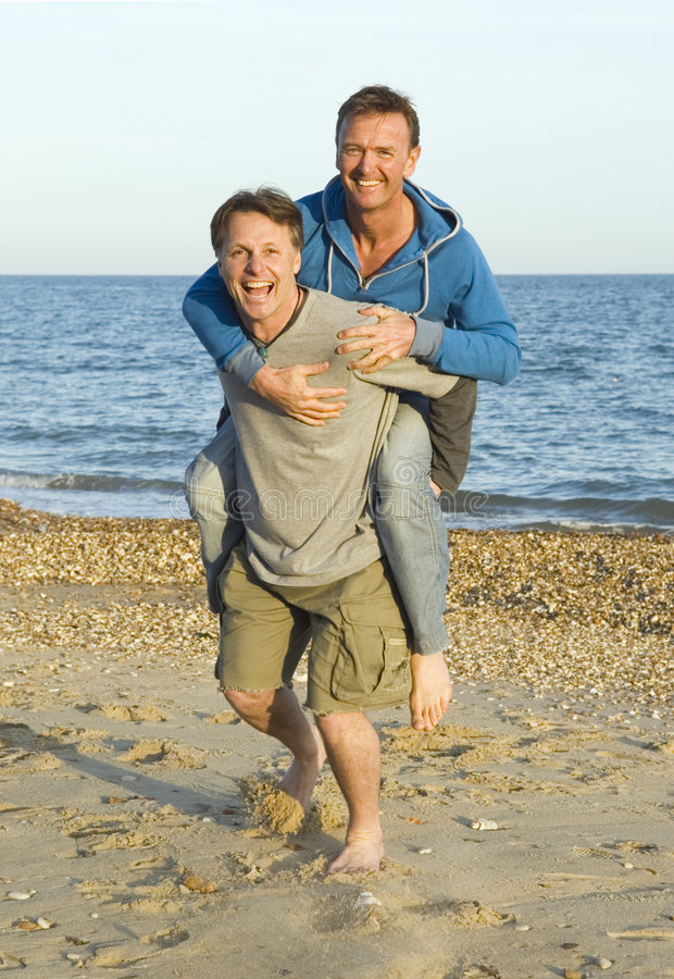 A happy gay couple. A homosexual couple are fooling around on the beach during their vacaton