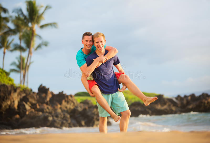 Happy gay couple. On the beach royalty free stock images