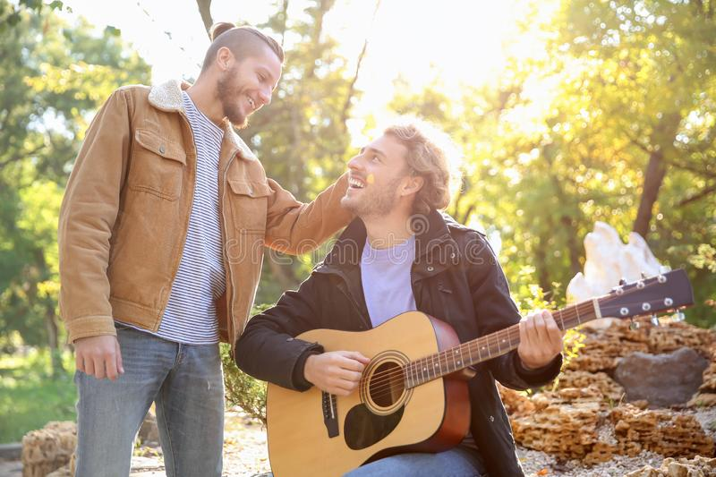 Happy gay couple with guitar in park royalty free stock photos