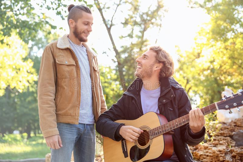 Happy gay couple with guitar in park stock photography