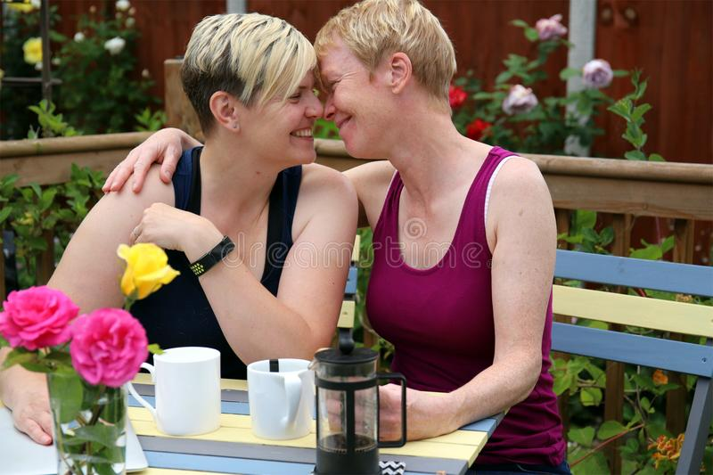 A happy gay couple at home in the garden, and embracing. Two adult middle aged feminine attractive gay women embracing in a garden full of roses on a summer day royalty free stock photo
