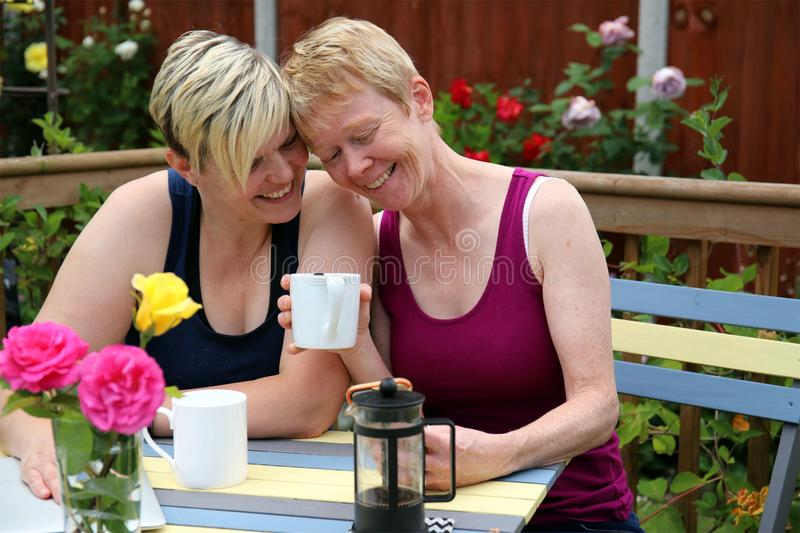A happy gay couple at home in the garden, and embracing. Two adult middle aged feminine attractive gay women embracing in a garden full of roses on a summer day royalty free stock images