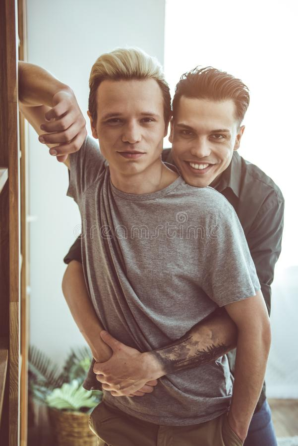 Happy gay couple hugging and looking at camera with smiles. Waist up portrait of handsome guy with dyed hair leaning against wooden wall unit while his boyfriend stock photo