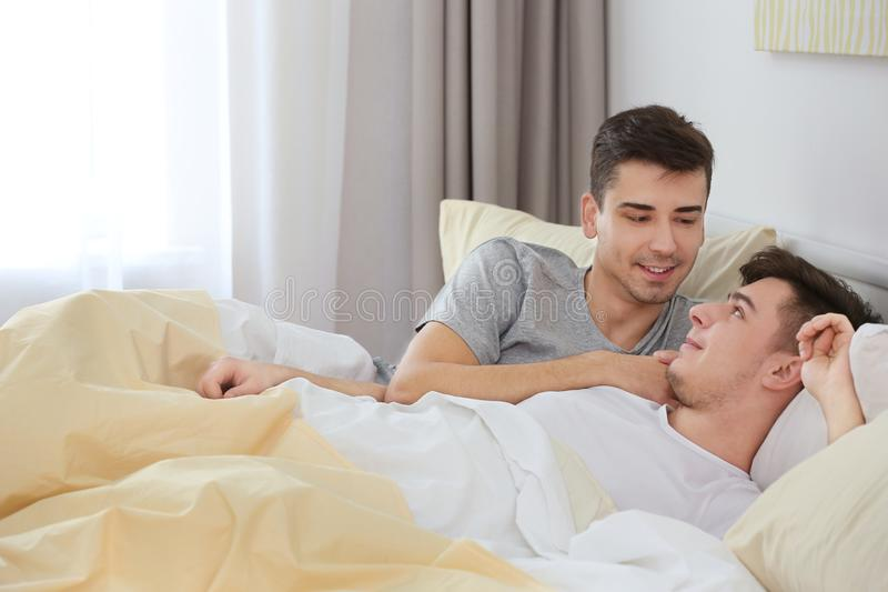 Happy gay couple lying in bed royalty free stock images