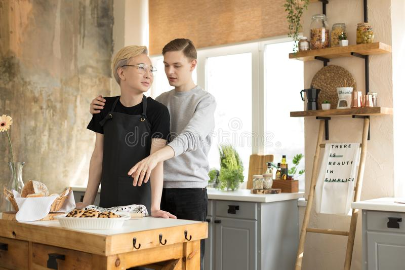 Happy gay couple, one asian with blonde hair in glasses second european in casual wear having breakfast in the kitchen royalty free stock image