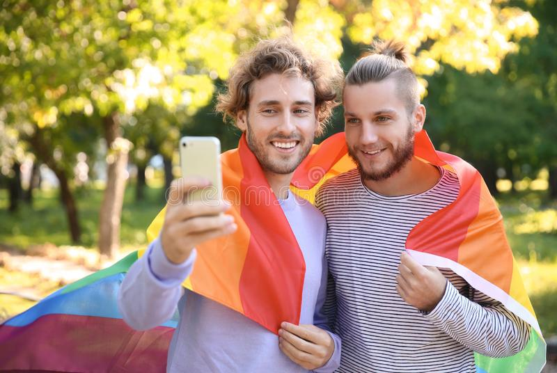 Happy gay couple taking selfie with rainbow LGBT flag in park stock photography