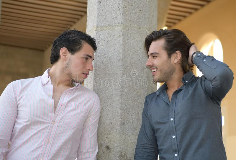 Happy gay couple talking relaxed stock photography