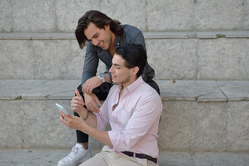 Happy gay couple with their mobile phone royalty free stock photography