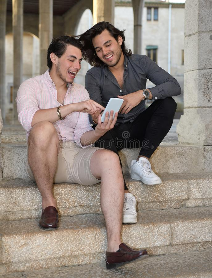Happy gay couple with their mobile phone stock photography