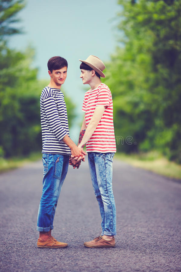 Happy gay couple together on spring road royalty free stock image