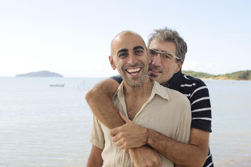 Happy gay couple on vacation royalty free stock photography