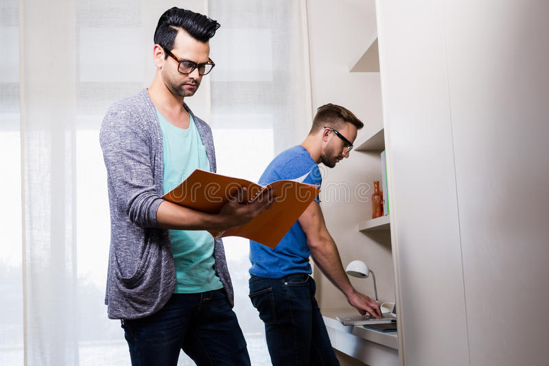 Happy gay couple working together. In office royalty free stock image