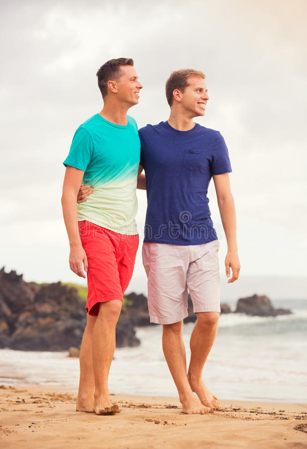 Happy gay couple. Young happy gay couple walking on the beach stock image