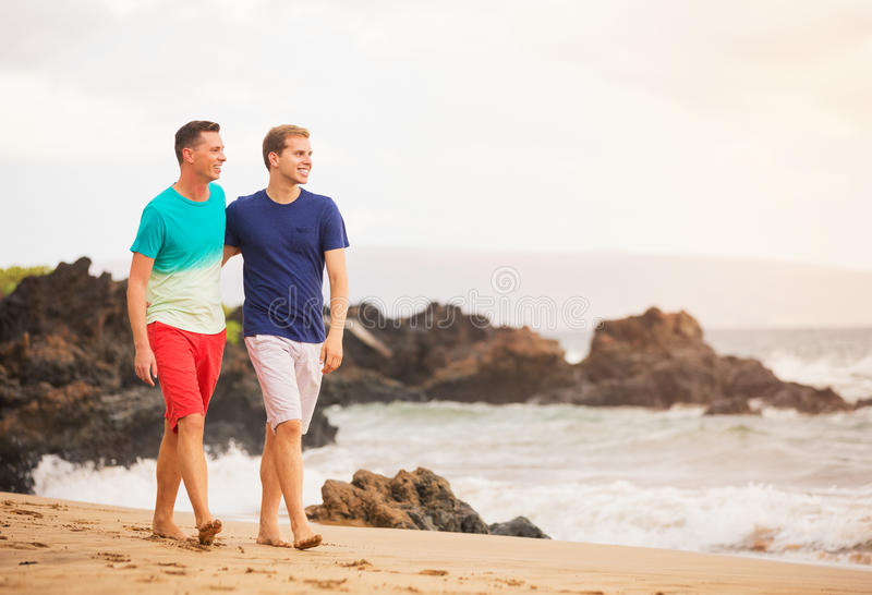 Happy gay couple. Young happy gay couple walking on the beach stock images