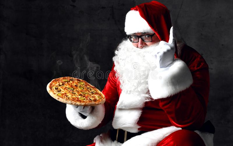 Happy and generous Santa Claus is holding steaming hot pizza eating showing one finger up. New year and Merry Christmas. Fast food concept royalty free stock photography