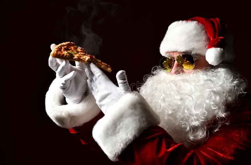 Happy and generous Santa Claus is holding steaming slice of hot pizza eating. New year and Merry Christmas. Fast food concept stock photography