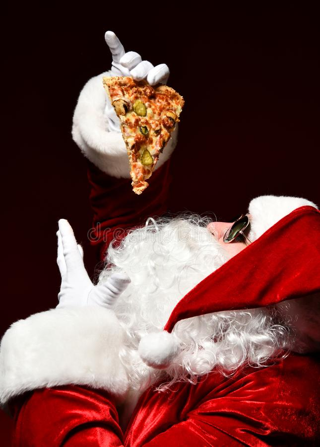 Happy and generous Santa Claus is holding steaming slice of hot pizza eating. New year and Merry Christmas. Fast food concept royalty free stock photo