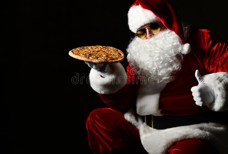 Happy and generous Santa Claus is holding tasty pizza on his open palm, showing thumb up. New year and Merry Christmas. Happy and generous Santa Claus in stylish stock photo