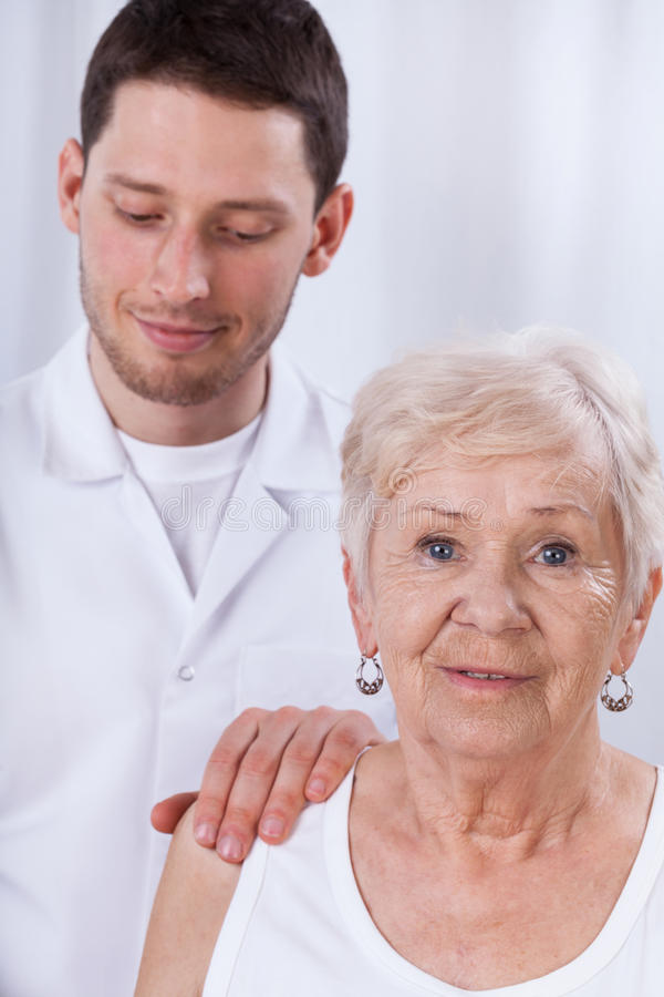 Happy geriatric patient. Closeup of doctor and his geriatric patient royalty free stock photo