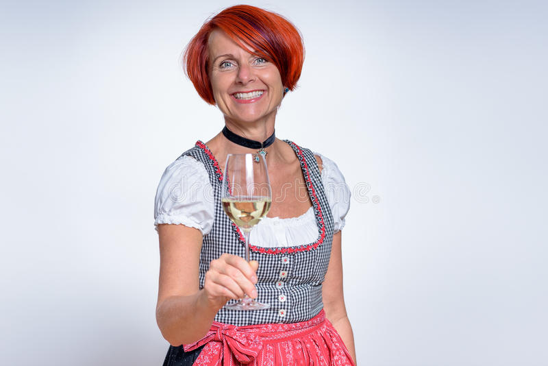 Happy German Woman Holding a Glass of Wine. Half Body Shot of a Happy German Woman in Dirndl Dress, Holding a Glass of Wine and Smiling at the Camera Against stock image