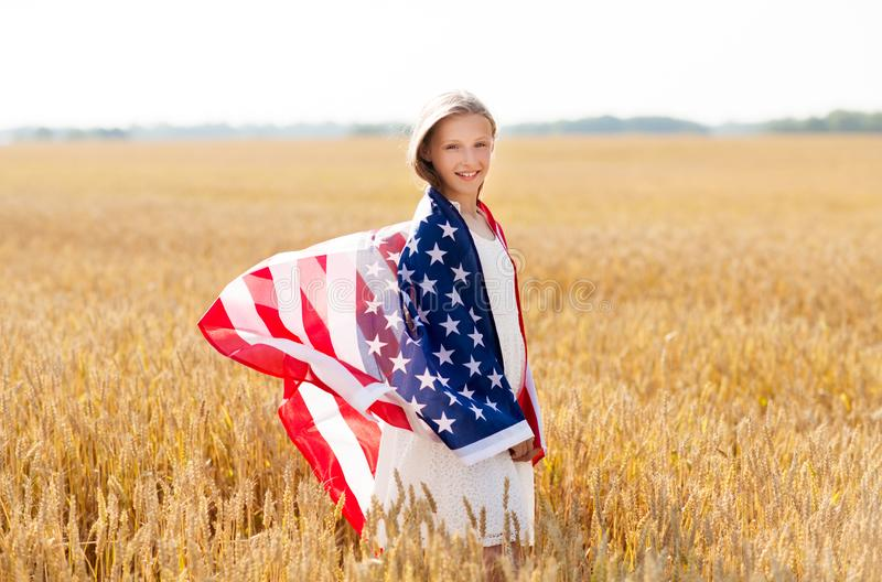 Happy girl in american flag on cereal field royalty free stock photos