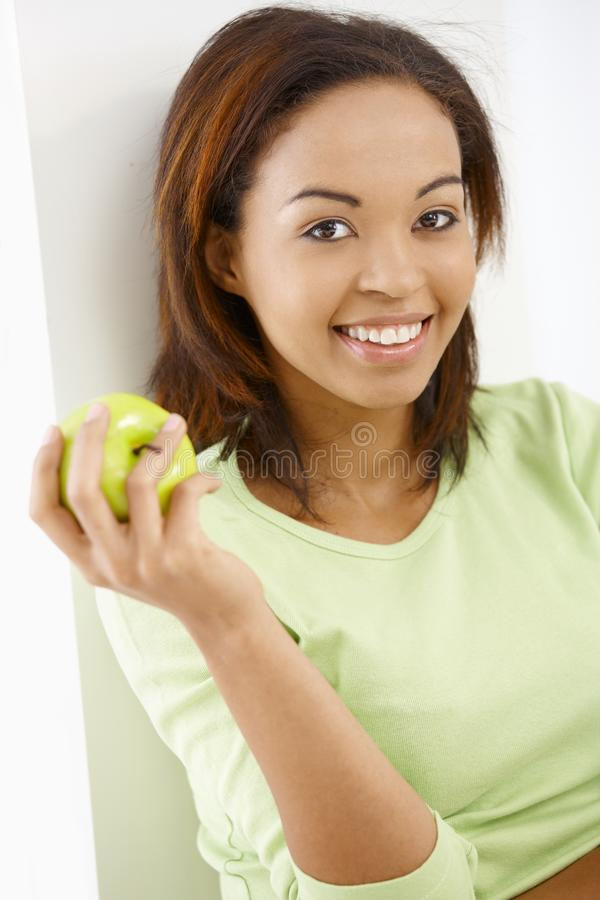Happy girl with apple. Portrait of happy afro girl smiling at camera with apple handheld stock photo