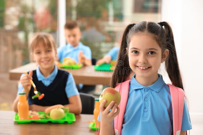 Happy girl with apple in school. Healthy food royalty free stock photo