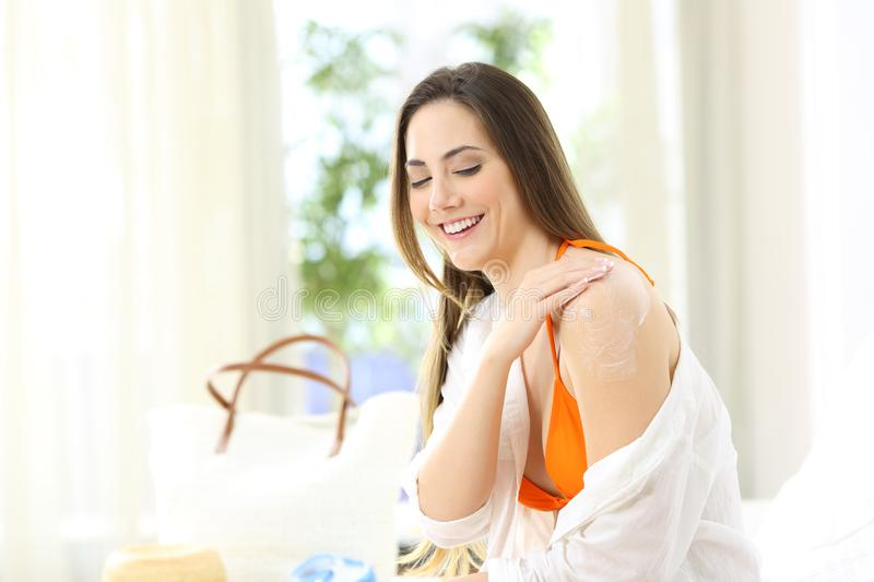 Girl applying sunscreen on shoulders in an hotel room royalty free stock photo