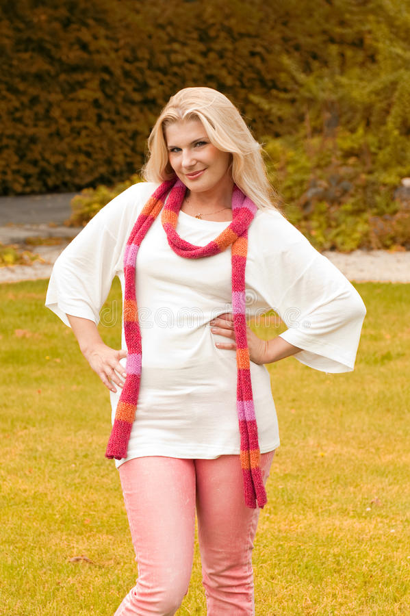 Happy girl in autumn park with a pink scarf royalty free stock photos