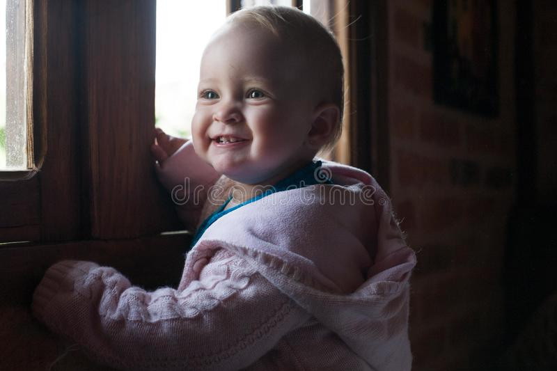 Happy baby girl smiling close to the window stock images