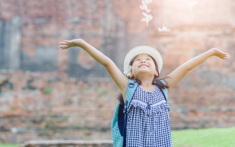 Happy girl with backpack play flower. On old temple background, lifestyle and travel concept stock photography
