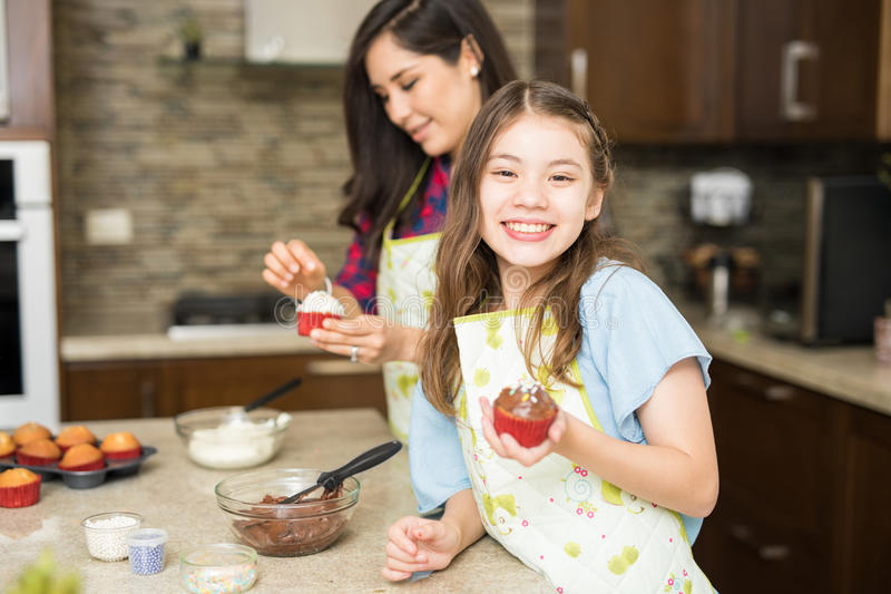 Happy girl baking with her mom. Portrait of a beautiful Hispanic girl holding a chocolate cupcake while baking with her mom at home stock photo