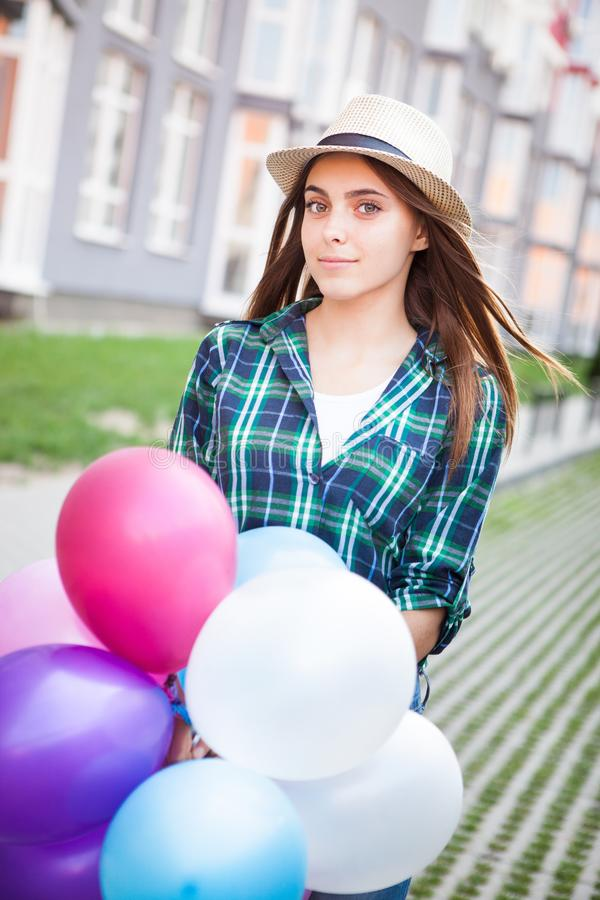 Happy girl with balloons on the street stock photo
