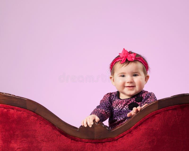 Happy girl behind sofa stock photos