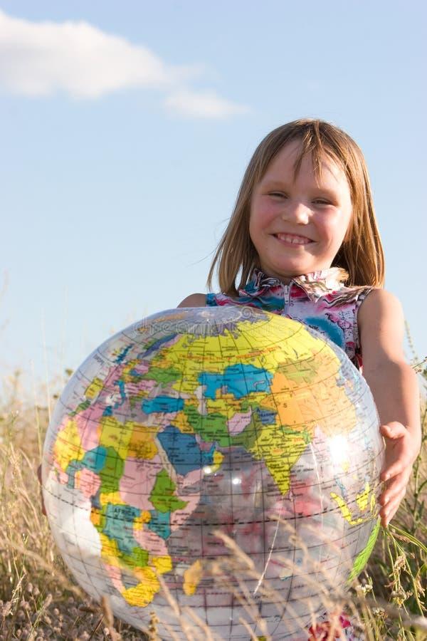 Happy girl with big globe stock photography