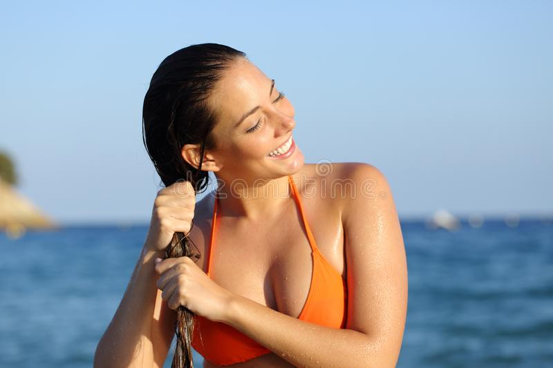 Happy girl in bikini draining hair after bath on the beach stock photography