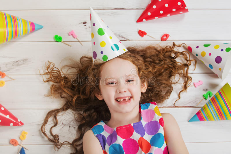 Happy girl in birthday party. Happy laughing girl in birthday party lying on wooden floor royalty free stock photos
