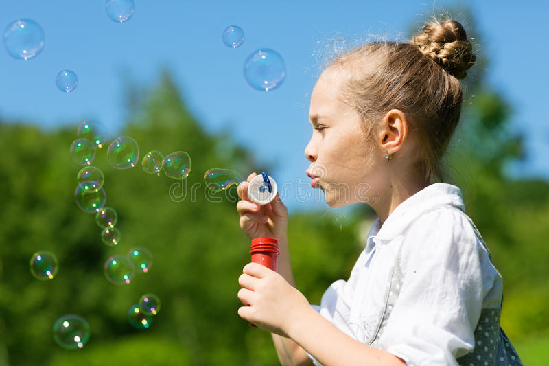 Happy girl blowing soap bubbles stock photo