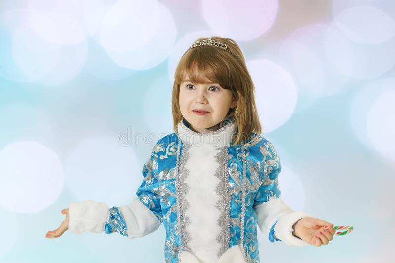 Happy girl in a blue costume of snow maiden with astonishment threw up his arms to the side royalty free stock photo